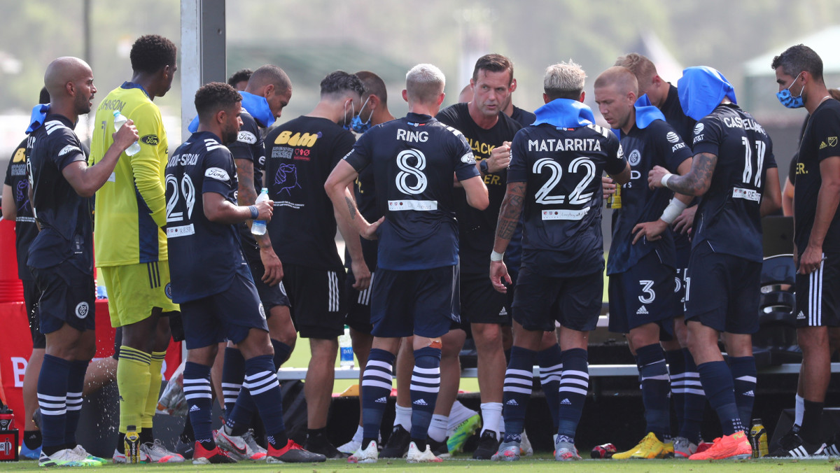 Jul 9, 2020; Kissimmee, FL, USA;  New York City FC head coach Ronny Deila talks with midfielder Alexander Ring (8), defender Ronald Matarrita (22) and teammates during the first half against the Philadelphia Union at ESPN Wide World of Sports.